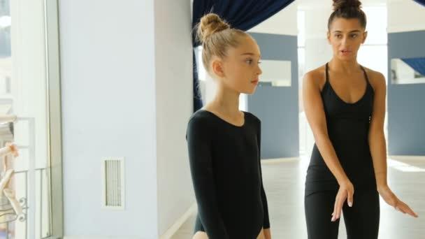 Portrét roztomilý dívka a její mladý učitel dělá nácvik některé prvky v baletní studio na pozadí města
