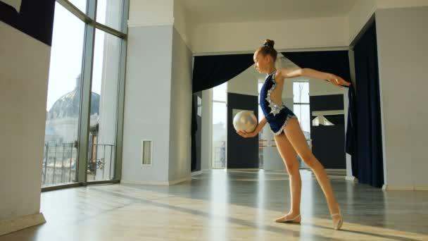 Mladá krásná dívka v modrých těla dělá gymnastické cvičení s míčem v ateliéru na pozadí města