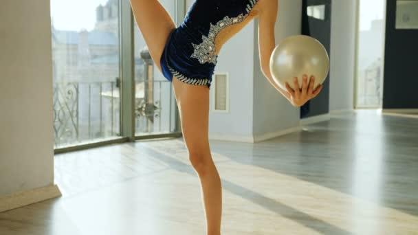 Portrét roztomilý gymnastka uvedení nohy s míčem v rukou, při pohledu na fotoaparát a usmívá se. Detailní záběr