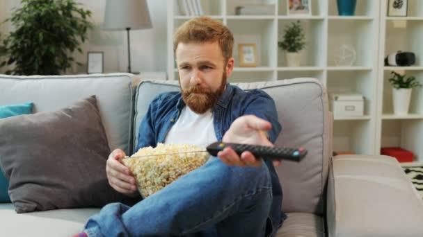 Fiatal seriuos ember pattogatott kukoricát eszik, és érdekes filmek a tévében keres kanapé a nappaliban ülve.
