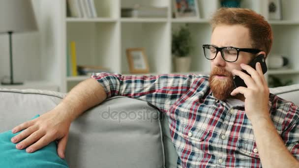Vonzó komoly ember beszél az üzleti partnerekkel szúró telefon közben pihentető a kanapén, otthon a nappaliban glasess.