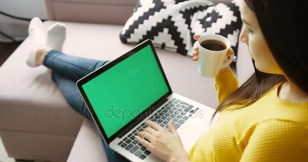 Mladá žena pomocí přenosného pc s zelenou obrazovkou, pití kávy, zatímco sedí na gauči v obývacím pokoji. Pohled zezadu. Chroma klíč