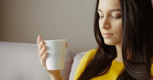 Atraktivní mladá žena sedí na gauči, pití kávy, čaje a pomocí chytrého telefonu. Chatování, surfování na internetu. Zblízka. Zpomalený pohyb