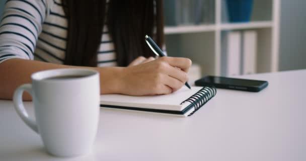 Közelről nőt írásban Jegyzettömb, jegyzetfüzet, az irodában. Megjegyezni a nő kezét. Közelről