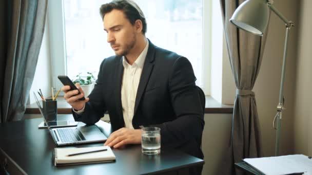 Mladí vážné obchodní muž dělá nějakou práci na chytrém telefonu, než začít používat přenosný počítač pro práci v kanceláři.