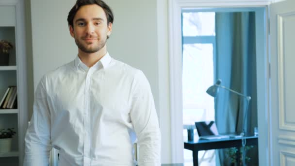 Happy caucasian man with beard in white shirt composing hands, looking at camera and smiling. Indoor.