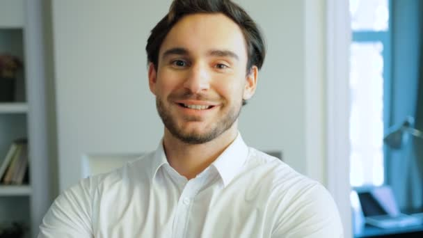 Portrait of smiling young man in white shirt. Happy caucasian man with beard looking at camera. Indoor.