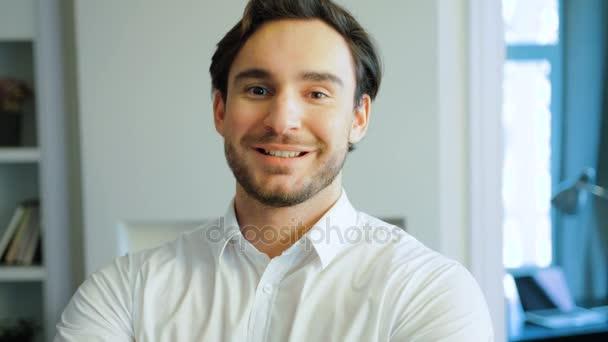 Portrét s úsměvem mladý muž v bílé košili. Happy kavkazské muž s plnovousem, při pohledu na fotoaparát. Vnitřní.