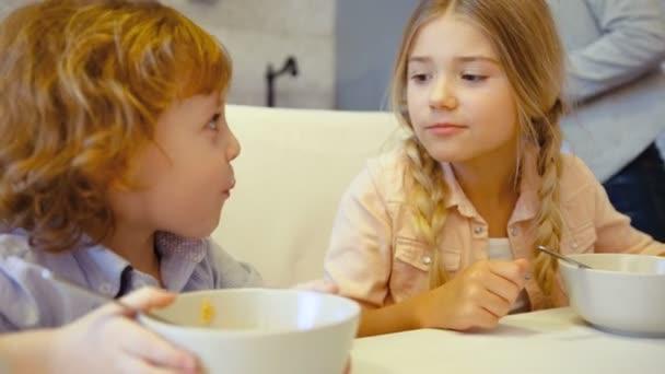 Kavkazské děti jíst vločky s mlékem umístění na bílém stole. Mladá rodina s brackfast a s úsměvem, umístění na stole v kuchyni