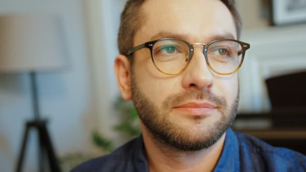 Portrét kavkazské atraktivní muž v brýlích s bradkou v modré košili, při pohledu na fotoaparát a usmívá se. Vnitřní.