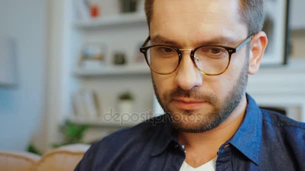 Portrét koncentrovaného kavkazské atraktivní muž v brýlích s vousem a tmavými vlasy v modré košili. Vnitřní