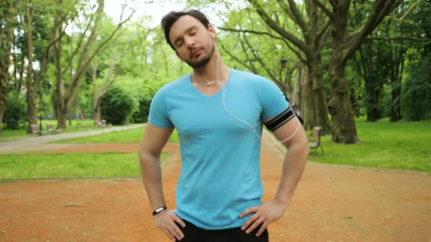 Handsome fitness man doing stretching exercises with head and neck in the park before run. Slow motion. Close up
