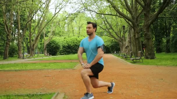 Young fit man doing stretching exercises in the beautiful green park before run. Slow motion.