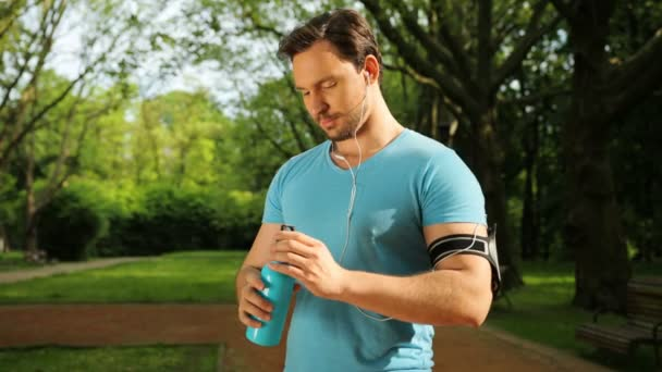Attractive man drinking water after jogging, running, fitness training. Refreshing after workout. Close up