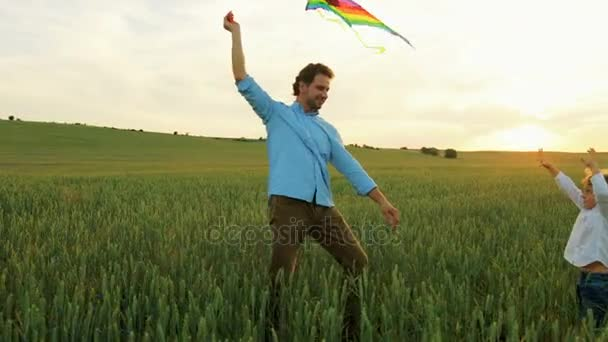 Smiling father and little son playing with colorful flying kite in green wheat field on sunset. Happy family