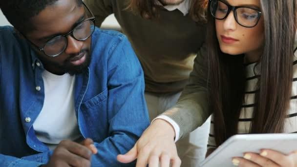 Detailní záběr záběr multi etnické obchodního týmu práci v moderní kanceláři s dokumenty a pomocí tabet
