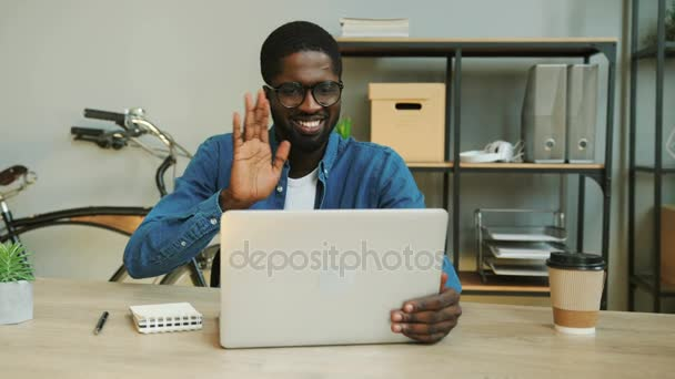 Close up shot of african young business man with glasses in blue denim shirt using laptop in the modern office for video chatting.