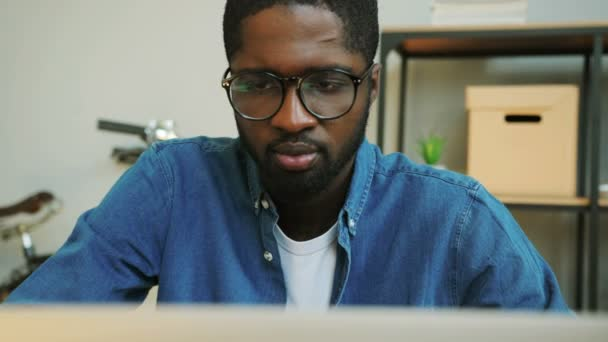 5ea0f3bc34b9 Close up shot of african young business man with glasses in blue denim  shirt working on the laptop in the modern office on the new finance  report.– stock ...