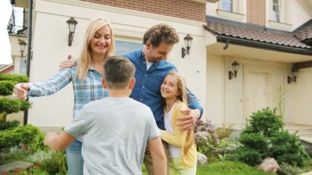 Šťastná rodina atraktivní pobyt před nový domov, syn a dcera běží k rodičům a objímání a usmívá se na kameru. Zblízka. Vnitřní záběr.