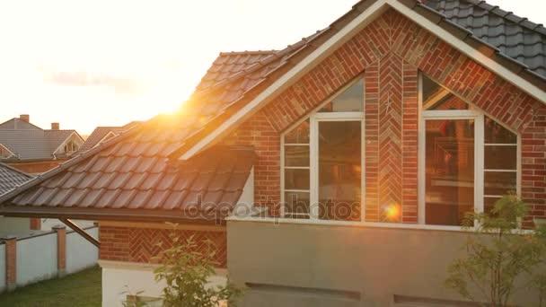 Közelkép panoráma lövés barna tető a modern ház idején a napsütés. Dolly lőtt..
