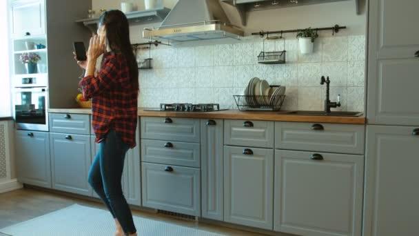 Krásná Kavkazský žena poslouchá hudbu a tanec v rytmu v moderní kuchyni.