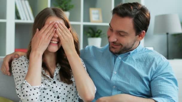 Portrét atraktivní muž překvapující svou emocionální přítelkyni kdo bankám oči s darem, zatímco oni sedí na gauči doma. Detailní záběr