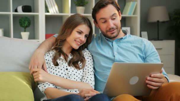 Emocionální atraktivní pár na dovolené na pohovce v obývacím pokoji při sledování filmu na přenosném počítači doma
