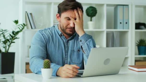 Business man getting very bad news on his laptop computer screen and feeling disappoint.