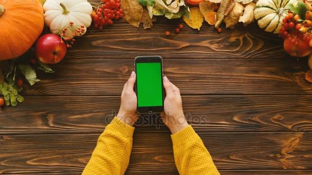 Zrušena plochý ležela s dýní, javorové listy na vrcholu dřevěný stůl. Žena ruce s černými smartphone s zelenou obrazovkou ve svislé poloze. Pohled shora. Chroma klíč