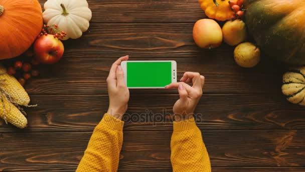 Ploché na podzim ležela s dýně, ovoce a zeleniny na hnědý dřevěný stůl. Žena, posouvání, klepnutí a zvětšování stránky na bílý chytrý telefon s zelenou obrazovkou v horizontální poloze. Chromatický klíč. Nahoru