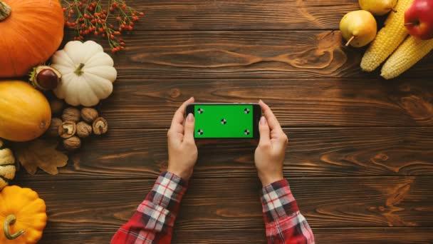 Ženské prsty rolování a posouvání stránky na černé smartphone s zelenou obrazovkou v horizontální poloze. Pohled shora tabulky s podzimní ovoce a zeleniny. Chromatický klíč. Sledování pohybu