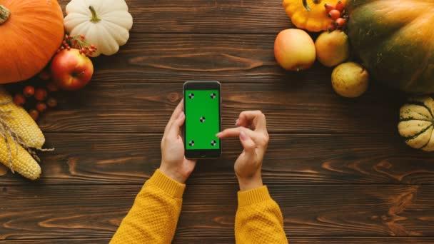 Pohled shora tabulky s podzimní tématikou. Černý smartphone s zeleným plátnem a ovoce a zeleninu na dřevěný stůl. Ženské prsty posouvání, klepnutí na dotykovém displeji. Chromatický klíč. Sledování