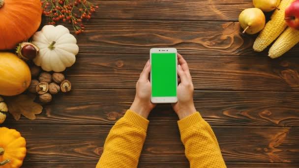 Žena používající bílý smartphone s zeleným plátnem na dřevěný stůl. Podzimní pohled shora s ovocem a zeleninou na stole. Chroma klíč