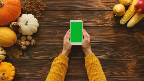 Bílý smartphone s zeleným plátnem na dřevěný stůl. Žena, Výčepní, transfokace na dotykovém displeji. Podzimní pohled shora s ovocem a zeleninou na stole. Chroma klíč