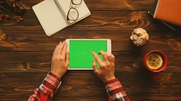 Herbstkonzept lag flach. Frau mit Tablet-Gerät mit grünem Bildschirm in horizontaler Position auf dem Holztisch. Ansicht von oben. Chroma-Schlüssel
