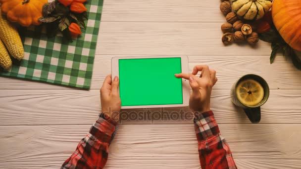 flach mit Obst, Nüssen und Gemüse auf dem weißen Holztisch. Frau blättert, tippt, zoomt Seiten auf Tablet-Gerät mit grünem Bildschirm. horizontale Position. Chroma-Schlüssel