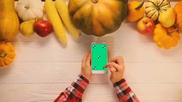 Draufsicht mit Gemüse, Obst und Smartphone mit grünem Bildschirm auf weißem Holztisch. flach lag. Chroma-Schlüssel. Scrollen, Zoomen.