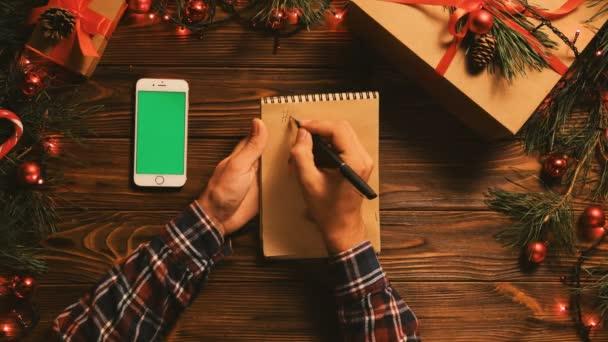 Az ember, írásban a notebook boldog új évet. Karácsonyi felülnézet lapos feküdt. Fehér smartphone-val zöld képernyő. Chroma-kulcs