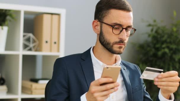 Sikeres fiatal üzletember szemüveg segítségével a hitelkártya és a smartphone részére online bevásárlás. Beltéri lövés. Közelről.