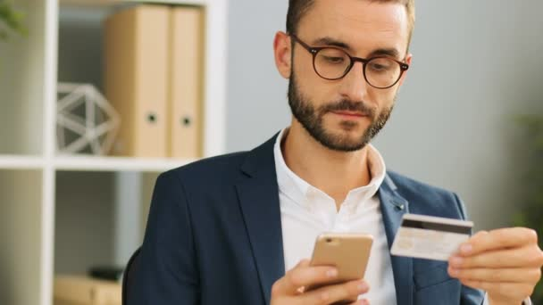 Successful young businessman in glasses and suit using his credit card and mobile phone for online shopping at the office desk. Indoor shot. Close up.