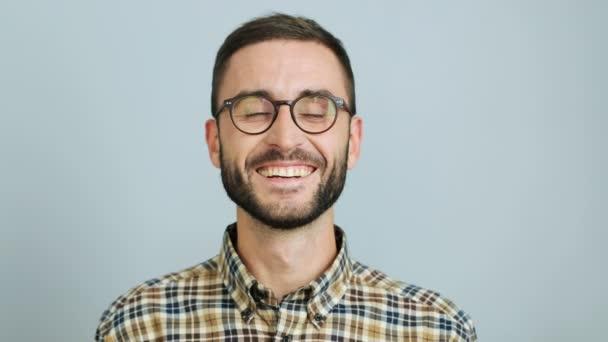 Zblízka zastřelil mladý pohledný muž v ležérní košile s úsměvem a ukazující vesele emoce na kameru na šedém pozadí. Venkovní snímek.