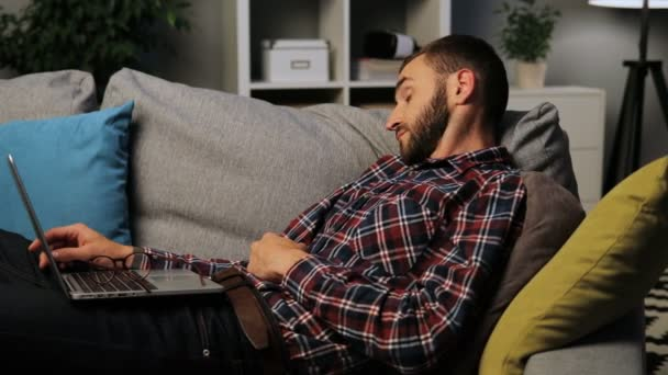 Attractive young man is sleeping on the couch with a laptop on his laps, after a short nap opens his eyes and put on the glasses. Indoor shot.