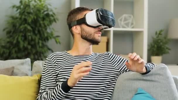 Kavkazská muž na sobě sluchátka pro sledování videa na šedém pozadí pozadí obývacího pokoje. Vnitřní