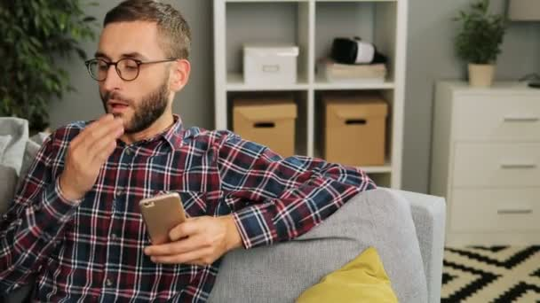 Young handsome man in glasses is sitting on the couch at home,holding the mobile phone and at the same time startes coughing. Indoor.