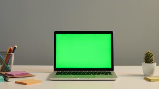 přenosný počítač s zeleným plátnem na stole