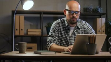 Bald-headed man work with laptop
