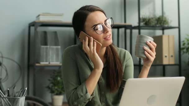 Atraktivní podnikatelka na mobilním telefonu a prochlastali káva při práci v moderní městské kanceláři. Detailní záběr