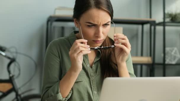 Krásný obchodní žena nasadil brýle při práci s přenosný počítač v moderní městské kanceláři. Žena čte s brýlemi. Detailní záběr