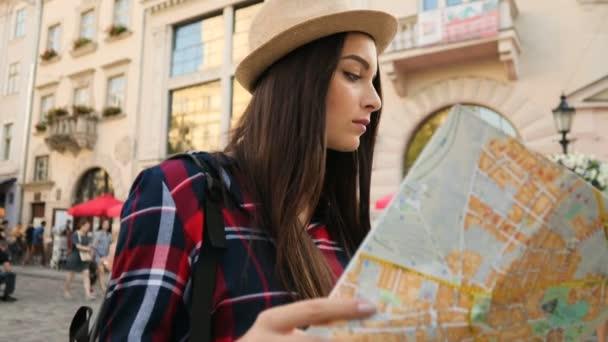 Mladá krásná žena Kavkazský s turistickou mapou hledá po celém městě ulici. Žena ztratila a snaží se najít správné ulici. Detailní záběr