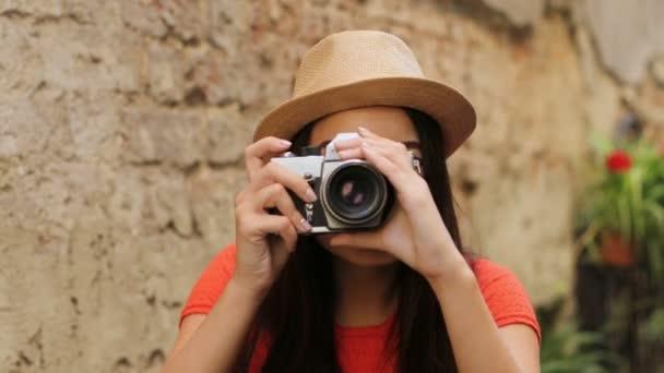 Portrét shot atraktivní usměvavá žena fotografování na její staré retro fotoaparát a díval se přímo do kamery. Detailní záběr
